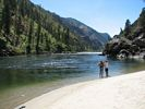 Two women standing on a white beach looking down the emerald green Salmon River