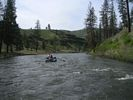 A raft floating through a long bend in the John Day River with grassy hillsides on both banks