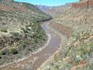 The brown Salt River winding through its canyon, with spotty vegetation on the steep cliffs and slopes of the canyon walls
