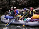 A whitewater raft with all occupants dressed in rain gear on the Middle Fork of the Salmon, Idaho
