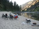 People sitting in folding chairs on a beach beside the Main Salmon River