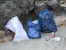 Three bags of river rafting trip garbage leaning against a rock