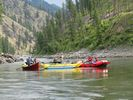 Bright red and yellow rafts, cats, and a dory on a calm section of the Main Salmon, Idaho