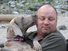 A dog giving a man a big wet kiss on the cheek