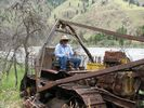 A man sitting on an abandoned bulldozer beside the South Fork of the Salmon River
